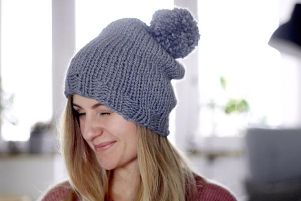 Dziewczyna wszarej czapce zpomponem, zrobionej nadrutach