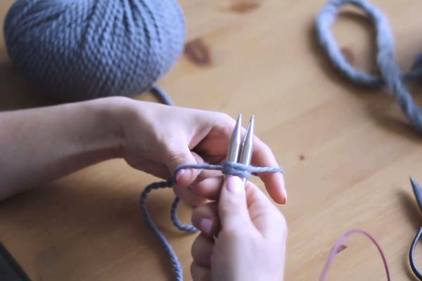 Dłonie, druty iwłóczka wtrakcie nabierania pierwszych oczek