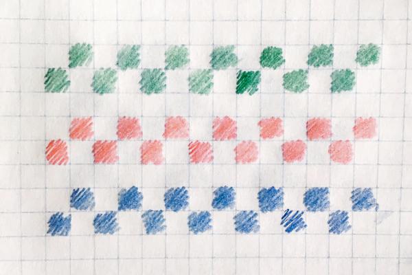 Schemat wzoru żakardowego narysowanego nakartce wkratkę: pasy kolorowych kwadracików.