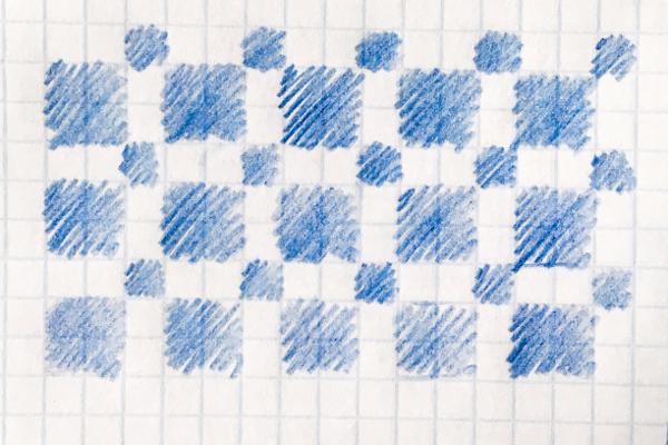 Schemat wzoru żakardowego narysowanego nakartce wkratkę: niebieskie kwadraciki, naprzemiennie wdwóch rozmiarach.