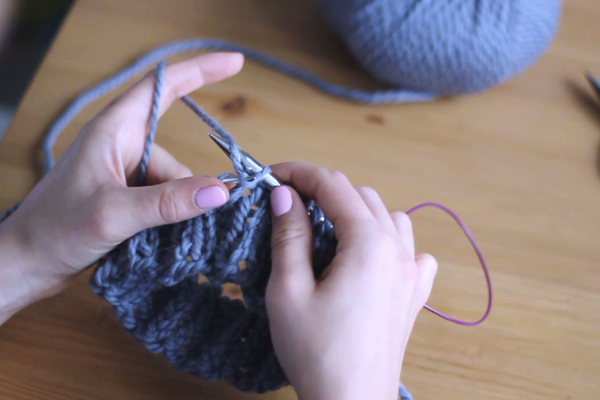 Dłonie trzymające druty, prawy drut wkłuty podpodniesioną nitkę nalewym drucie izahaczający nitkę odkłębka.