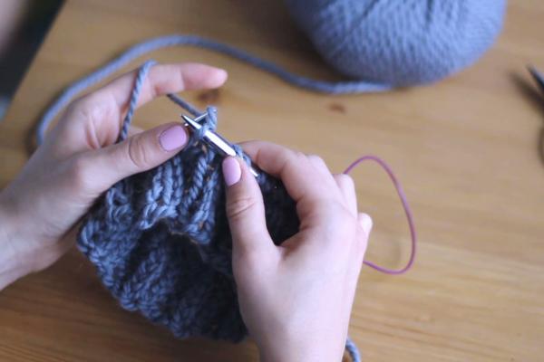Dłonie trzymające druty, prawy drut przeciągający nitkę przezoczko.