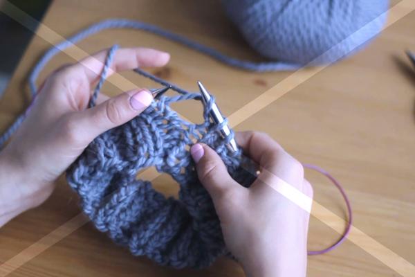 Dłonie trzymające druty, błędny sposób dodania oczka