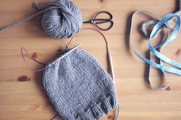 Szara czapka prawie zrobiona nadrutach, motek wełny, czarne nożyczki, centymetr krawiecki nastole.