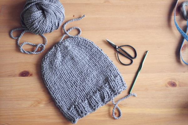 Szara czapka zrobiona nadrutach, motek wełny, czarne nożyczki, szydełko nastole.