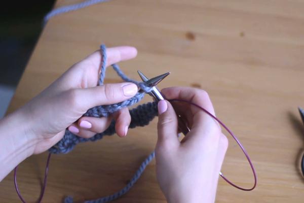 Dłonie trzymające druty iprzerabiające pierwsze oczko naprawo