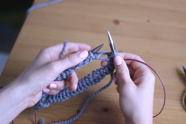 Dłonie trzymające druty iprzerabiające pierwsze oczko naprawo - zdejmowanie przerobionego oczka