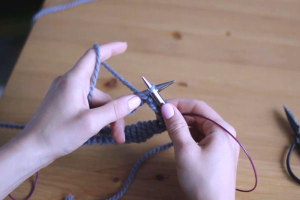 Dłonie trzymające druty, przerabiające lewe oczko