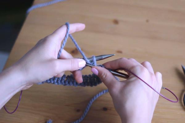 Dłonie trzymające druty, przerabiające lewe oczko - zahaczanie nitki