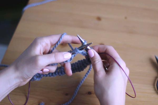 Dłonie trzymające druty, przerabiające lewe oczko - przeciąganie nitki
