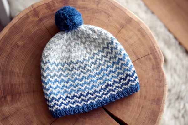 Biało-niebieska czapka wzygzaki zgranatowym pomponem rozłożona napłasko.