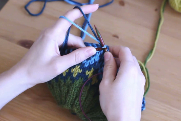 Czapka robiona nadrutach wzorem żakardowym trzymana wdłoniach.