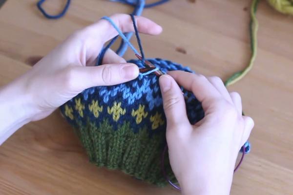 Czapka robiona nadrutach wzorem żakardowym trzymana wdłoniach. Zahaczanie pierwszej nitki.