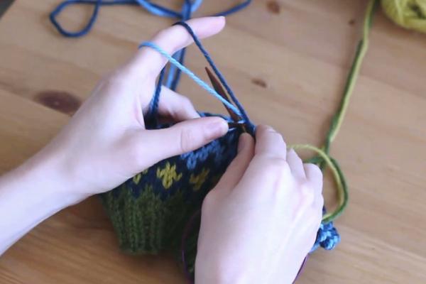 Czapka robiona nadrutach wzorem żakardowym trzymana wdłoniach. Zawijanie nitki - drut poniżej obu nitek.