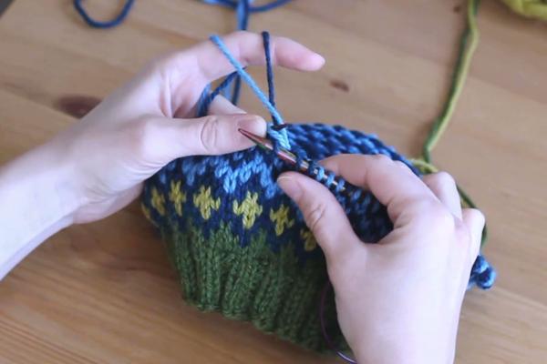 Czapka robiona nadrutach wzorem żakardowym trzymana wdłoniach. Przeciąganie nitki przezoczko.