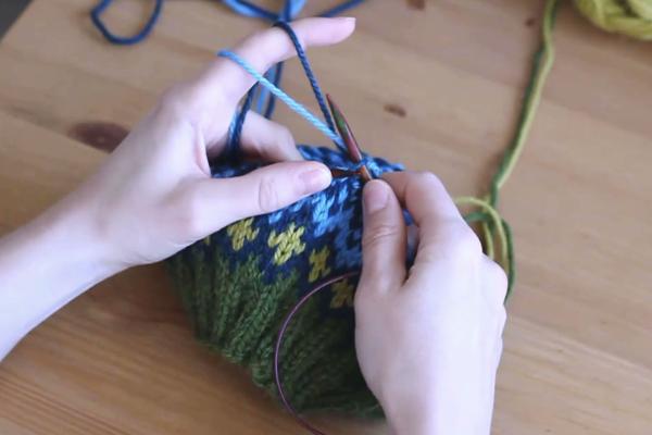 Czapka robiona nadrutach wzorem żakardowym trzymana wdłoniach. Powstało oczko