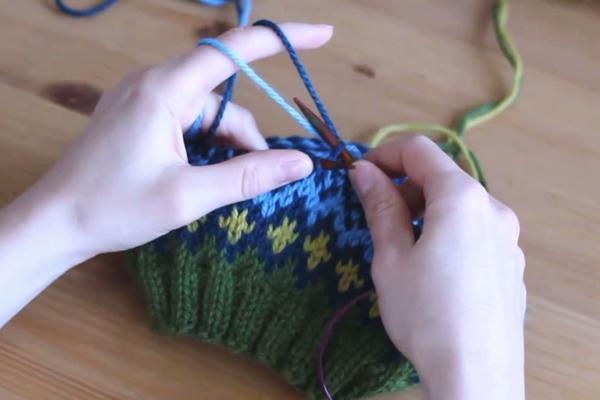 Czapka robiona nadrutach wzorem żakardowym trzymana wdłoniach. Oczko błękitne przerabiane normalnie, bezzawijania.