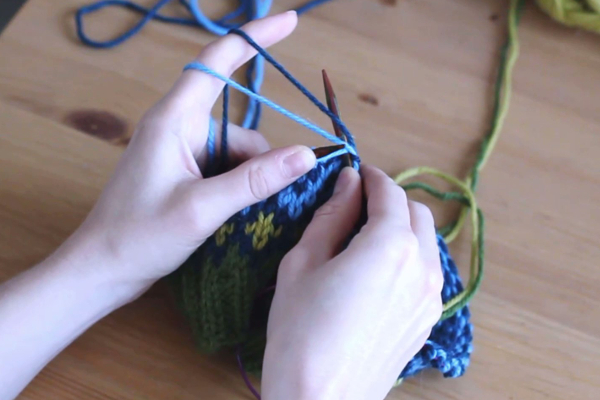 Czapka robiona nadrutach wzorem żakardowym trzymana wdłoniach. Zawijanie błękitnej nitki, drut poniżej obu włóczek.