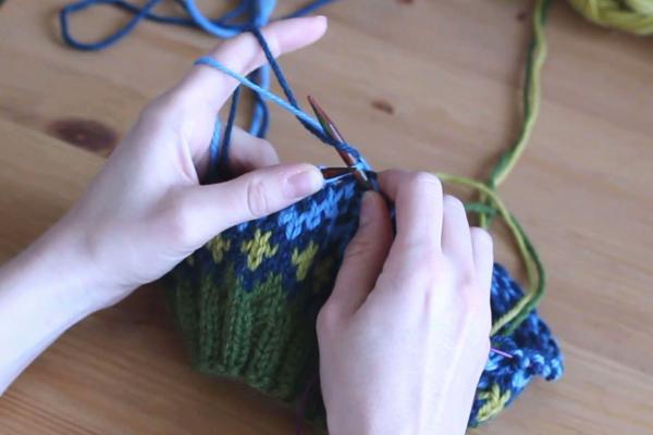 Czapka robiona nadrutach wzorem żakardowym trzymana wdłoniach. Zawijanie druta wokół włóczki błekitnej.