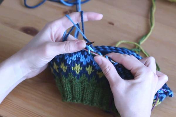 Czapka robiona nadrutach wzorem żakardowym trzymana wdłoniach. Powstaje błękitne oczko.