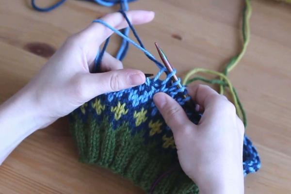 Czapka robiona nadrutach wzorem żakardowym trzymana wdłoniach. Powstało błękitne oczko.