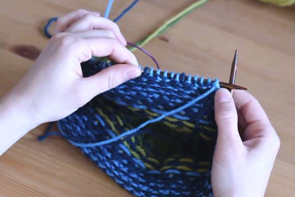 Czapka robiona nadrutach wzorem żakardowym trzymana wdłoniach. Lewa strona robótki, widać zawinięte nitki.
