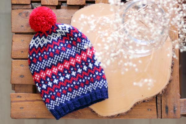 Granatowo-biało-czerwona czapka popinjay zwzorem żakardowym izpomponem ułożona napłasko nadrewnianym stoliczku zeskrzynek.