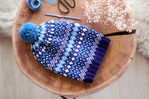 Granatowo-biało-niebieska czapka popinjay zwzorem żakardowym ipomponem, ułożona napłasko nadrewnianym stoliczku zpnia.