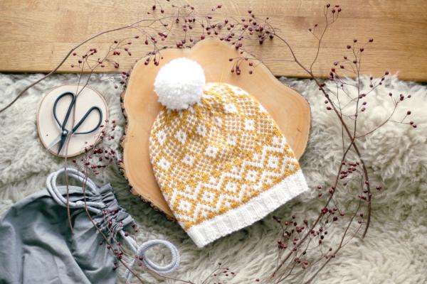 Czapka Goldenrod Hat, biało żółta zpomponem, ułożona nadrewnianej podkładce, otoczona suszonymi gałązkami.