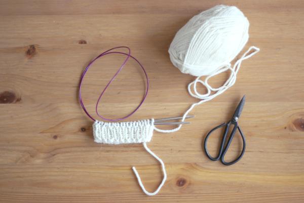 Ściagacz skarpetki zrobiony nadrutach białą włóczką.