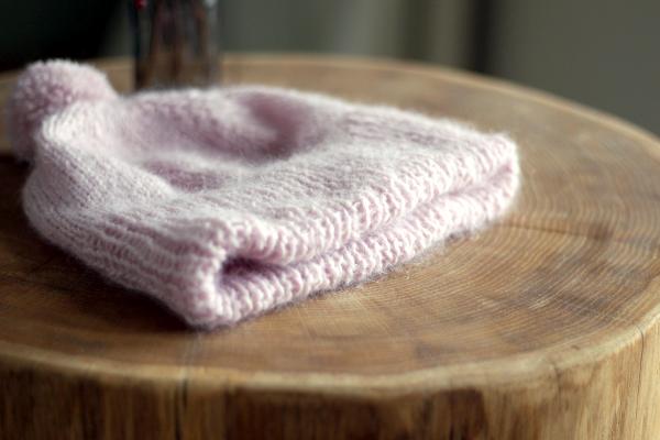 Czapka nadrutach wkolorze pudrowego różu położona nadrewnianym stoliku, tak, żewidać podwójnie złożony ściągacz.