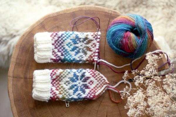Niedokończone rękawiczki znorweskim wzorem Selbu Rose położone nastoliku.