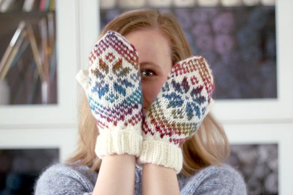 Dziewczyna wwełnianych rękawiczkach zwzorem, zakrywająca częściowo twarz.