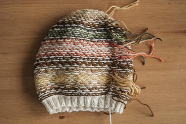 Lewa strona czapki żakardowej zwidocznymi nitkami przedich wrobieniem.
